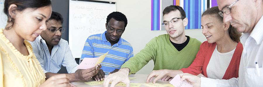 Collègues multiculturels assis autour d'une table. Milieu de travail respectueux. www.graybridgemalkam.com
