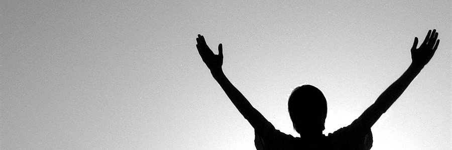 Silhouette of person with hands up in joy. personal wellness. www.graybridgemalkam.com